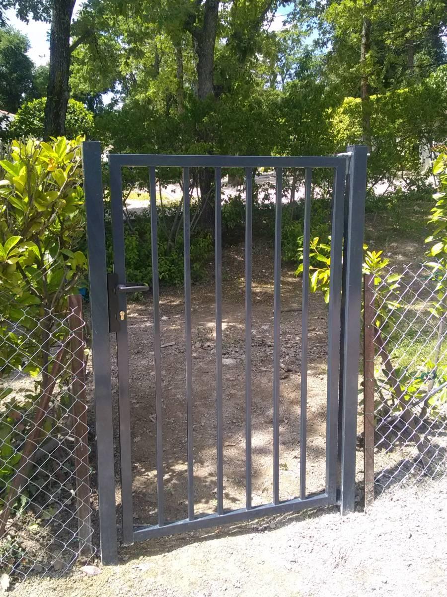 Paysagiste pose portillon baraudé gris dans un jardin avec piscine à ...